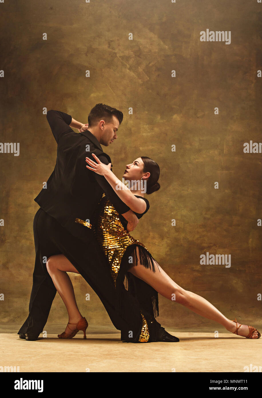 102942372 Dance ballroom couple in gold dress dancing on studio background ...