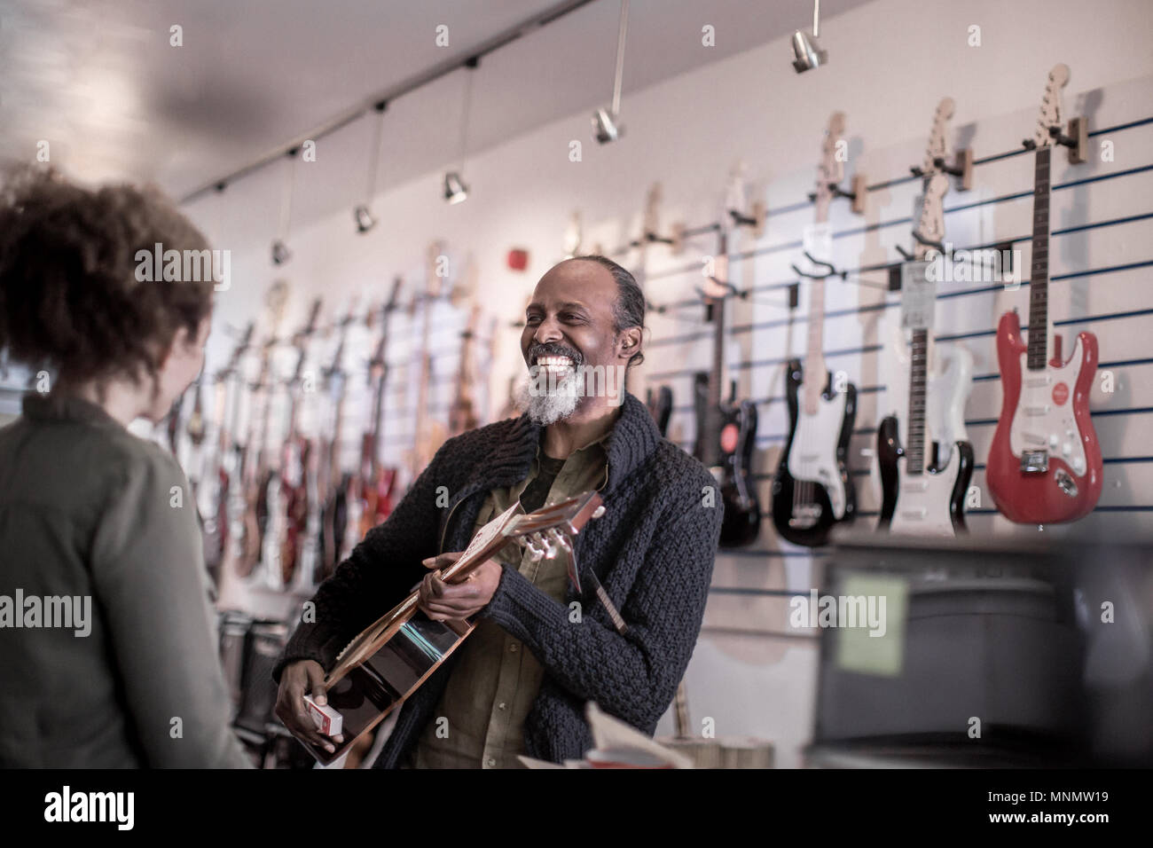 Senior male playing guitar in store Stock Photo