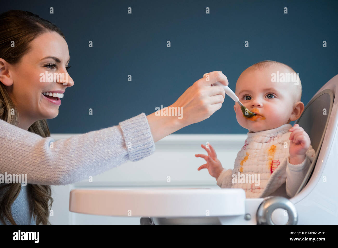 Mother feeding baby (18-23 months) - Stock Image