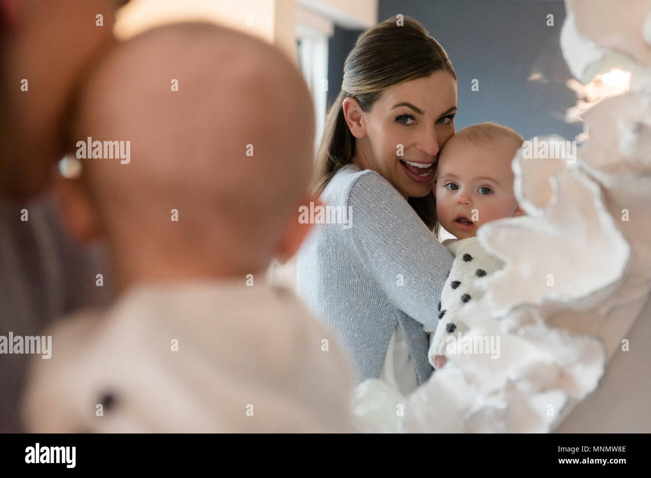 Mother holding baby (18-23 months) in front of mirror - Stock Image