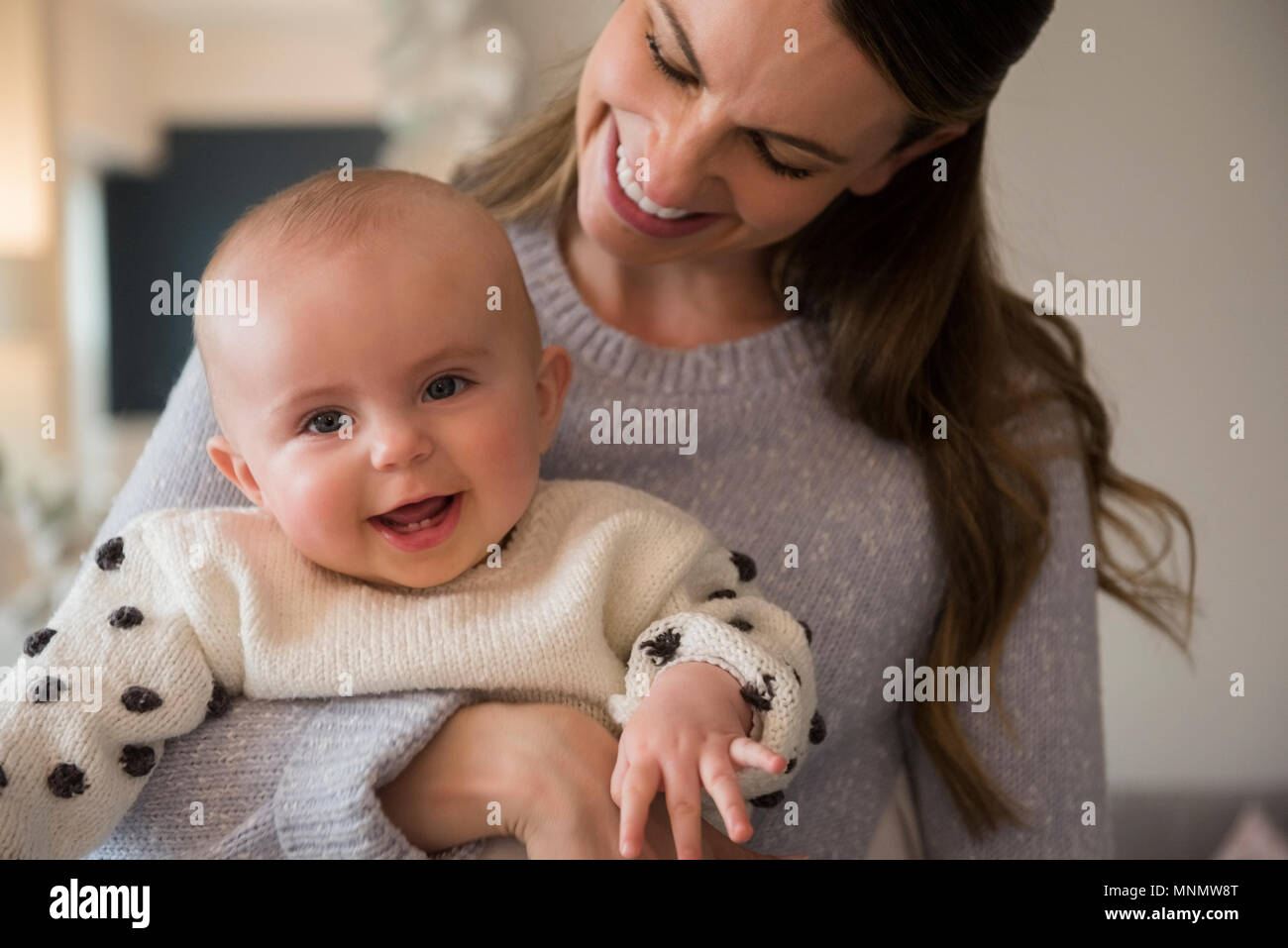 Mother holding baby (18-23 months) - Stock Image