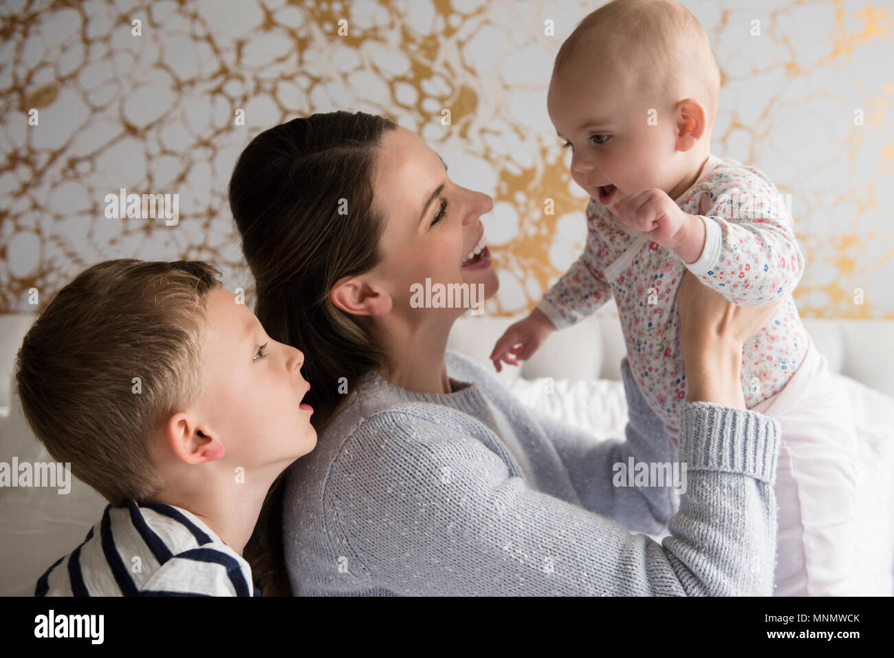 Mother playing with children (18-23 months, 4-5) - Stock Image