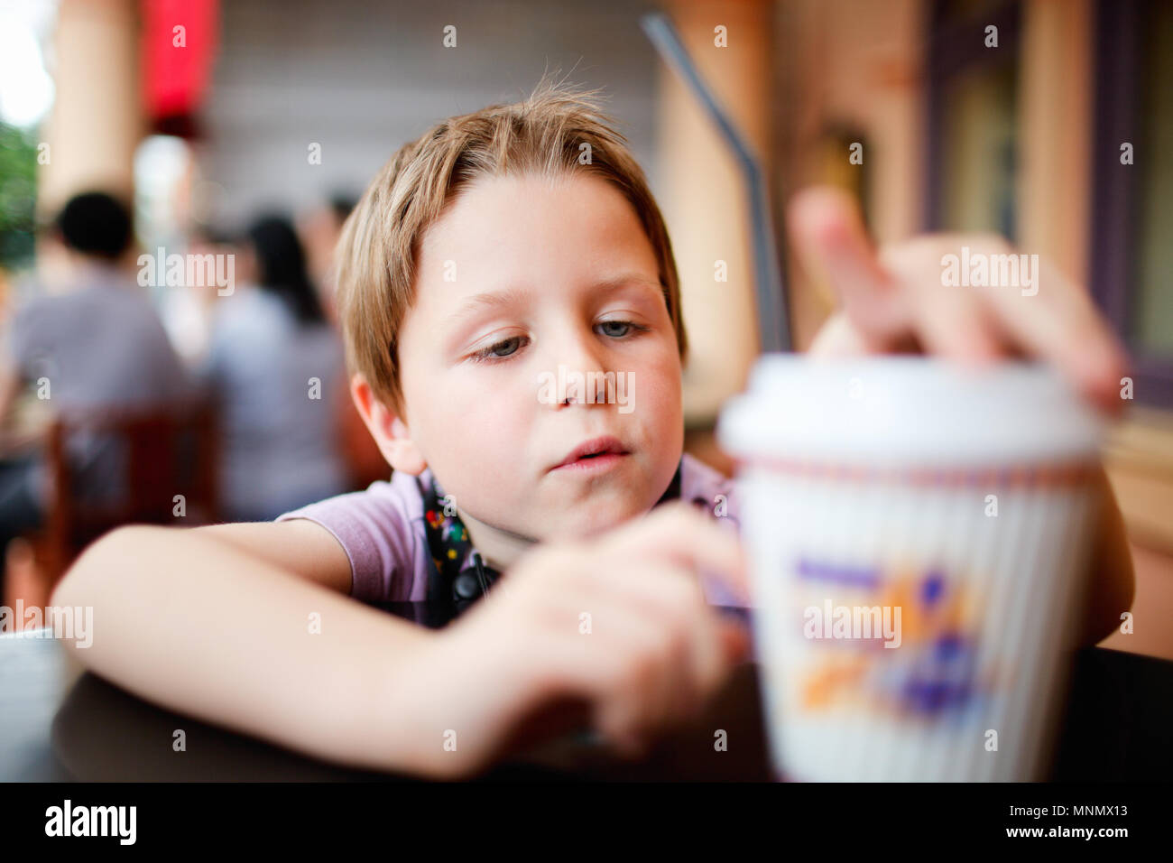 Casual portrait of little boy in cafe - Stock Image
