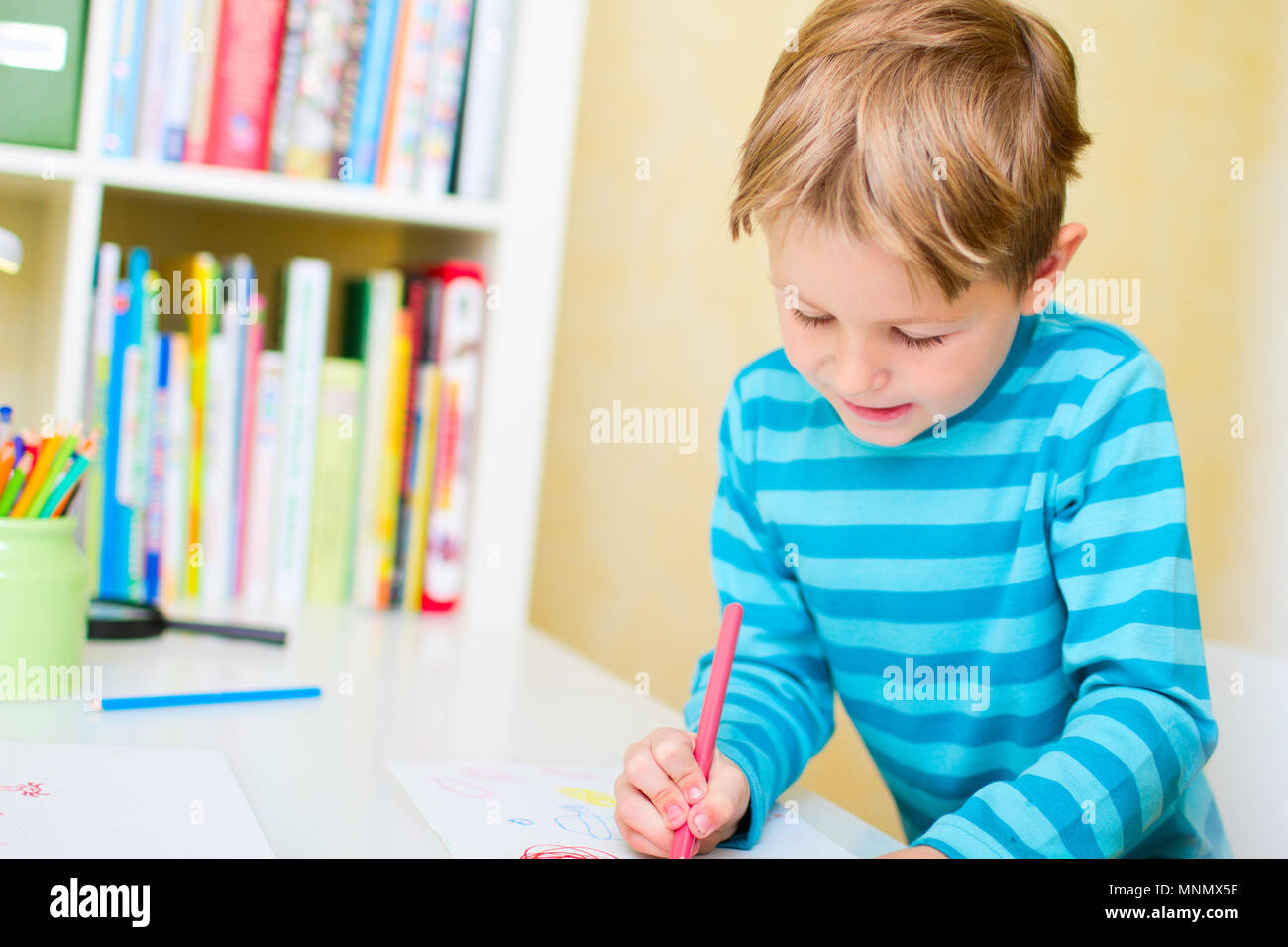 Portrait of cute happy schoolkid at home making homework - Stock Image