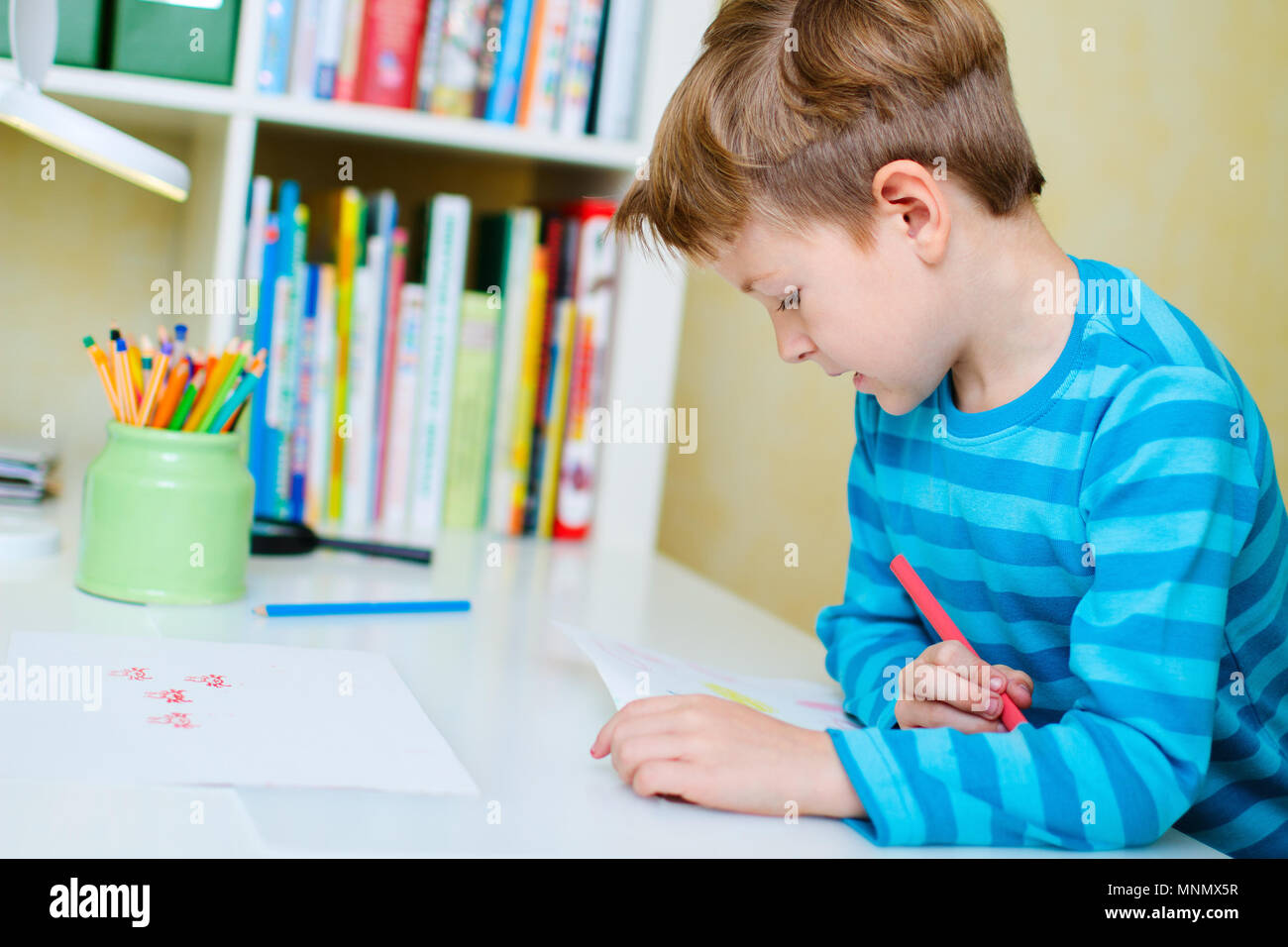 Cute happy schoolkid at home drawing or studying - Stock Image