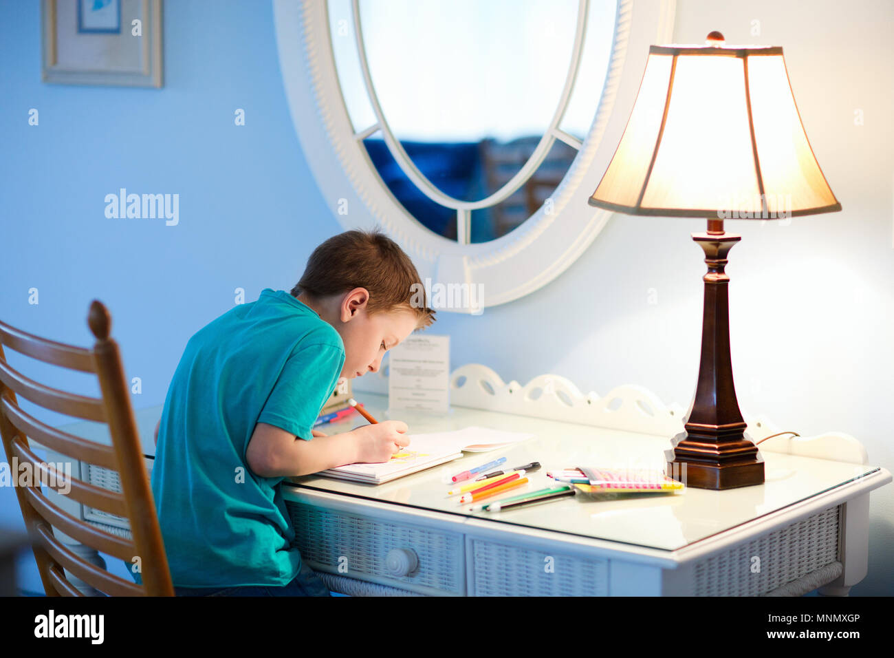 Portrait of cute happy schoolkid at home drawing or writing - Stock Image