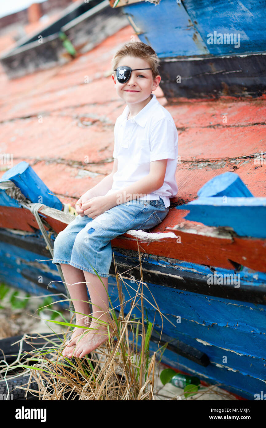 Outdoor portrait of cute pirate boy sitting at an old boat Stock Photo