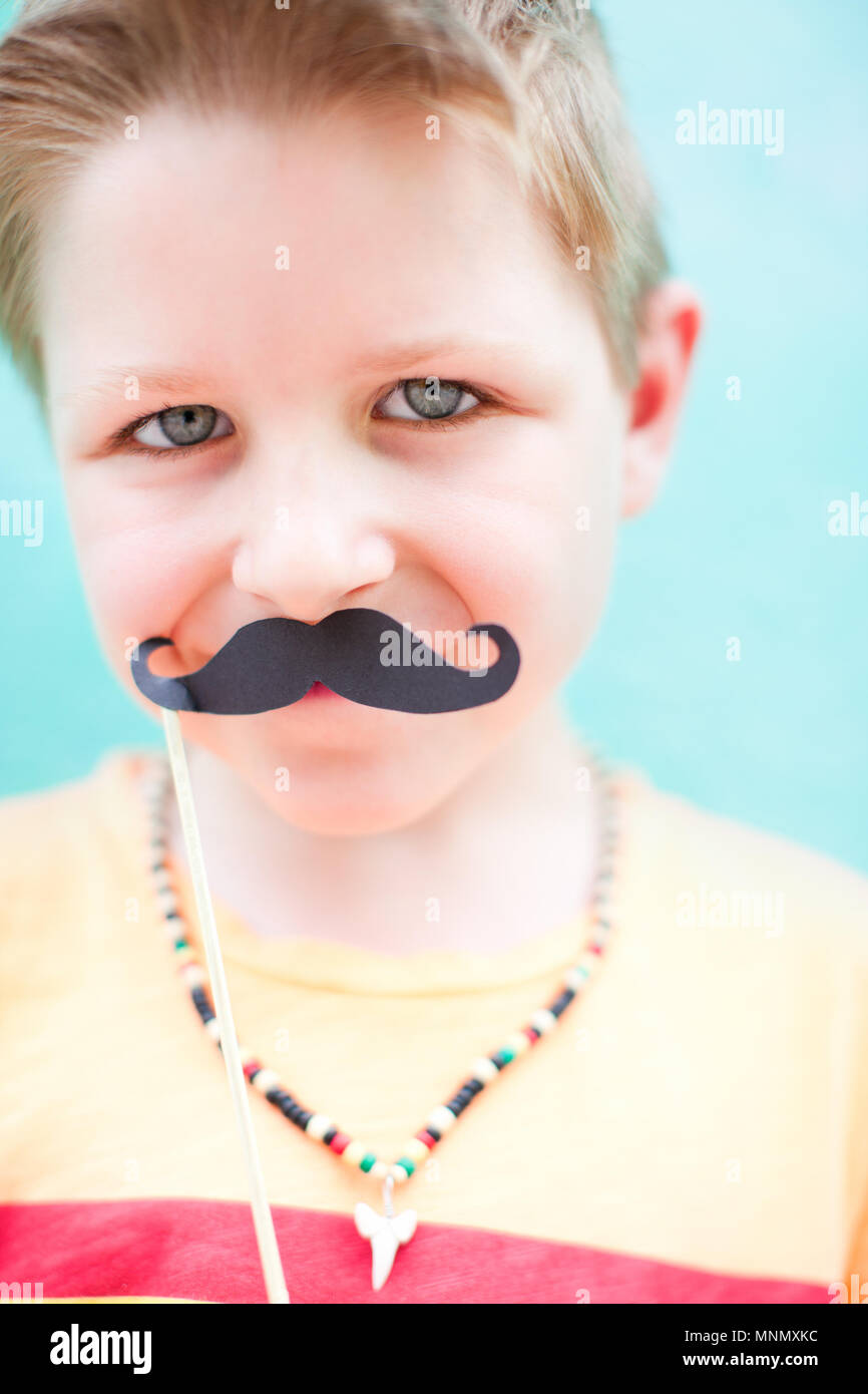 Cute boy holding mustache party accessory - Stock Image