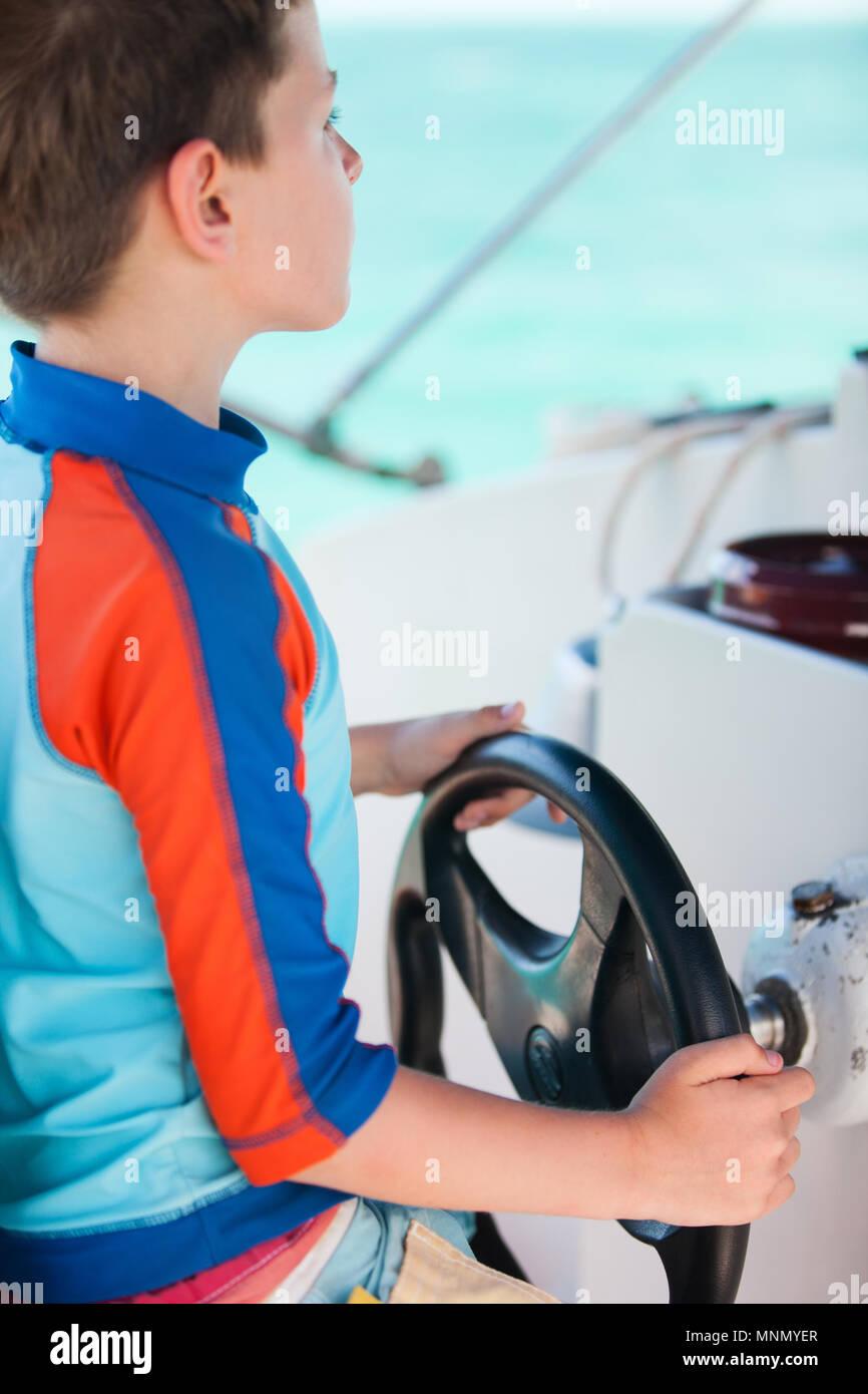Cute little boy at sail boat wheel - Stock Image