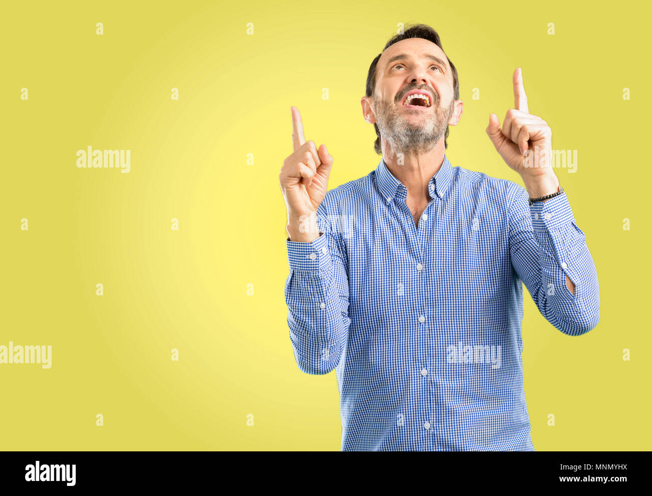 Handsome middle age man happy and surprised cheering pointing up - Stock Image