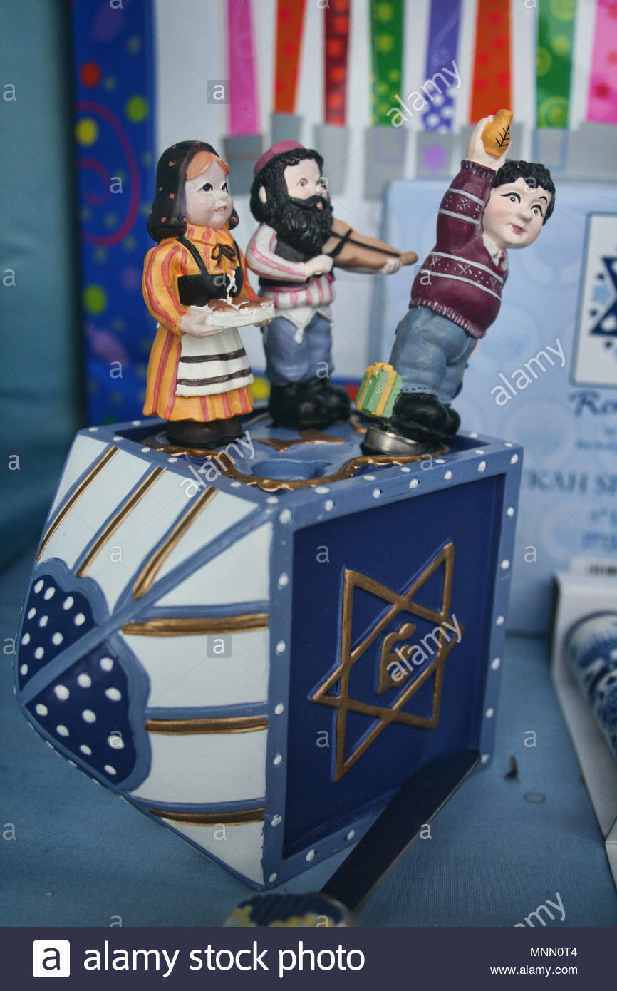 ceramic dreidel on its side with figures of a Jewish family. A dreidel is a spinning top with letters of the Hebrew alphabet on each side. It is playe - Stock Image