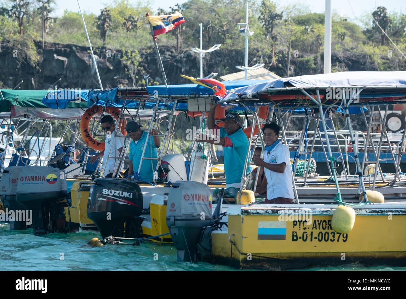 Water taxis captains in the harbor in Puerto Ayora, Santa Cruz Island, Galapagos Islands, Ecuador. - Stock Image