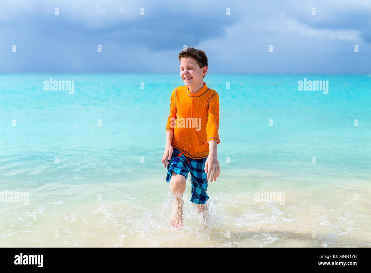 Cute boy in sun protection rash guard at tropical beach on summer vacation - Stock Image