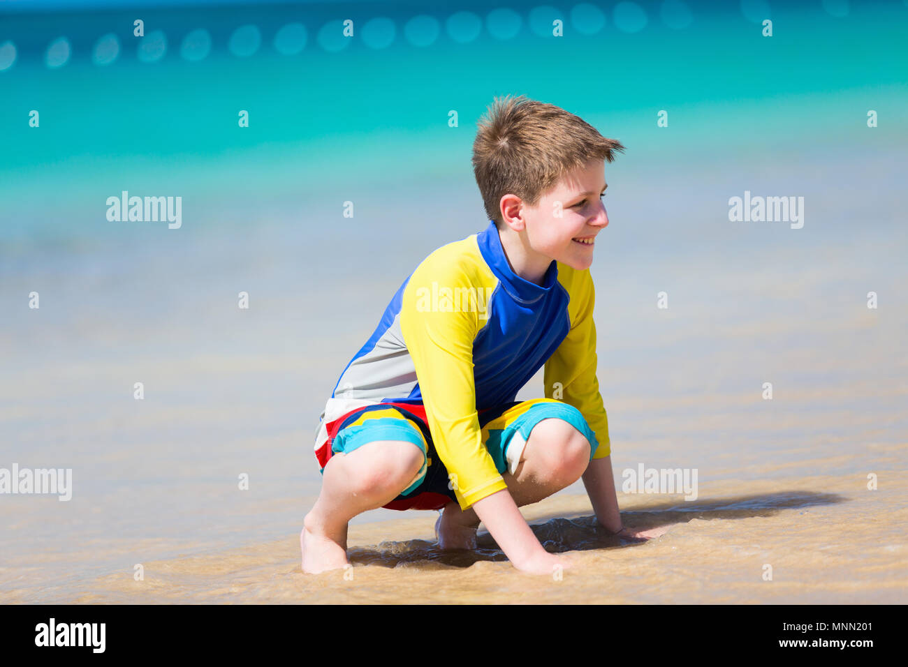Handsome pre-teen age boy playing with sand at tropical beach on summer vacation - Stock Image
