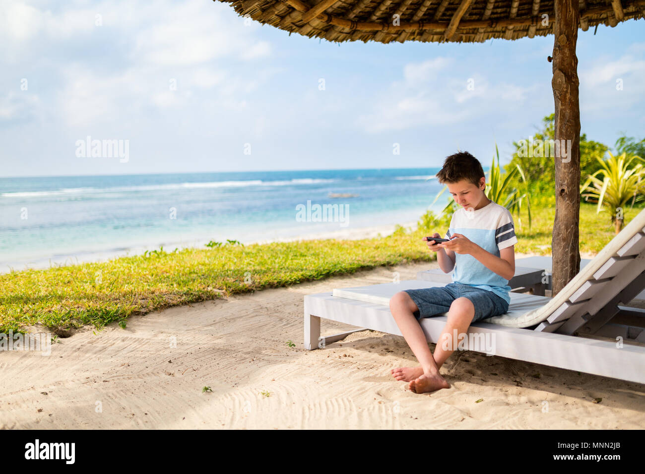 Handsome pre-teen age boy playing on phone at tropical beach on summer vacation - Stock Image