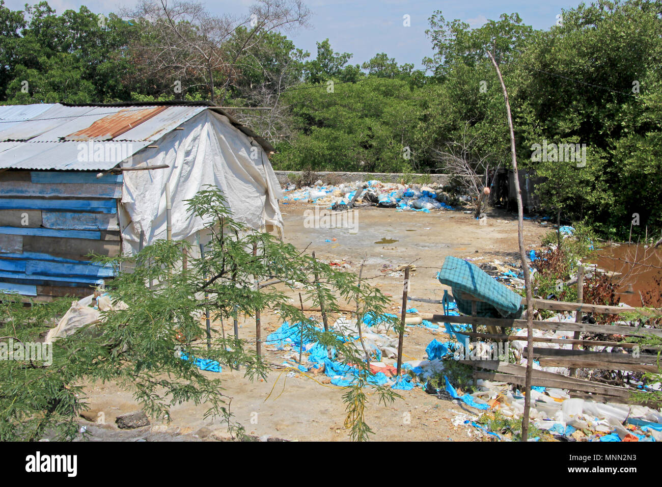 Littering of garbage in front of private houses along colombian coast, Santa Marta, Columbia - Stock Image