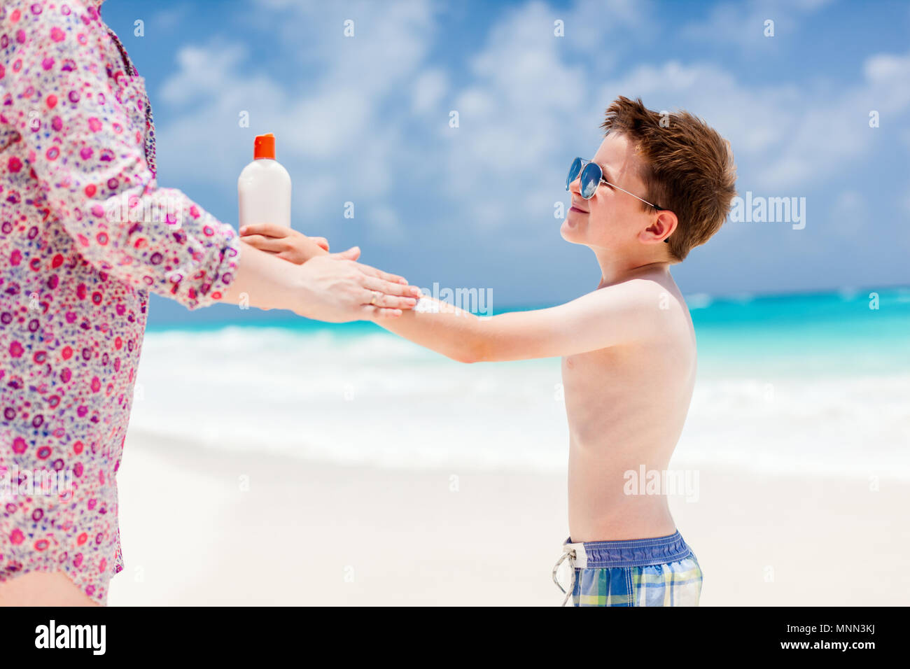 Close up of a mother applying sunblock cream on her son - Stock Image