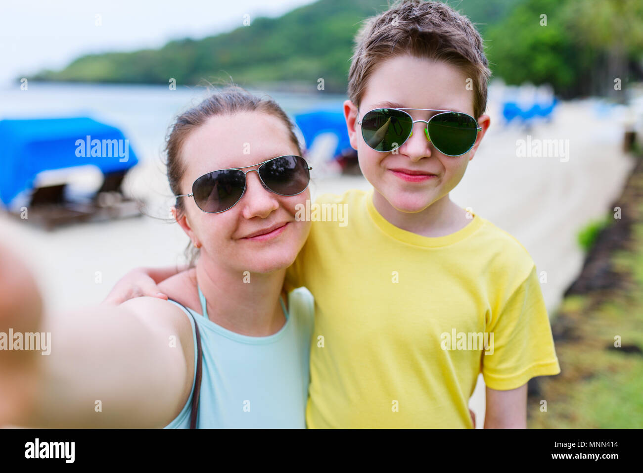 Happy family mother and son at beach taking selfie - Stock Image