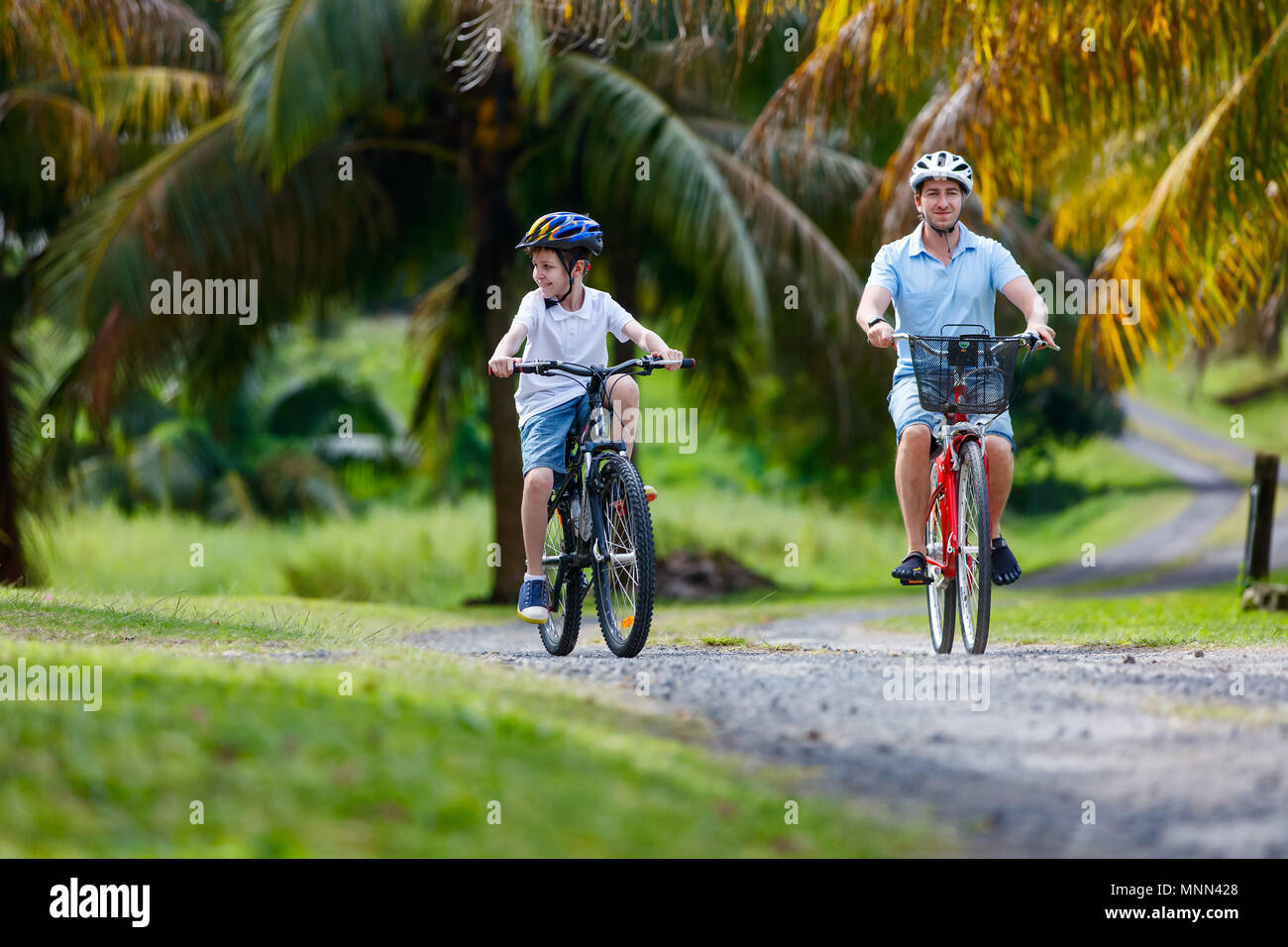 Family of father and son biking at tropical settings - Stock Image