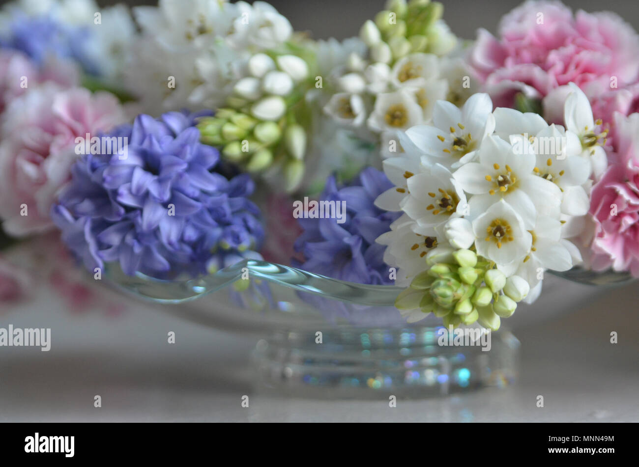 Closeup Of Pink White And Purple Wedding Flowers In A Glass Bowl
