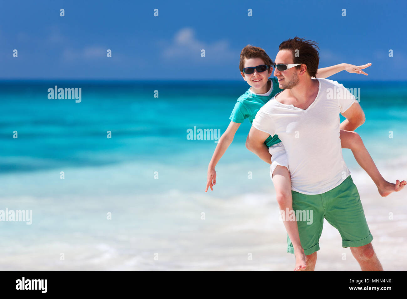 Happy father and son enjoying time at beach during family vacation - Stock Image
