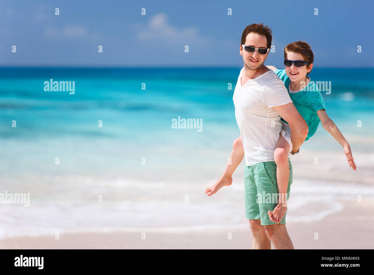 Portrait of happy father and son enjoying time at beach - Stock Image