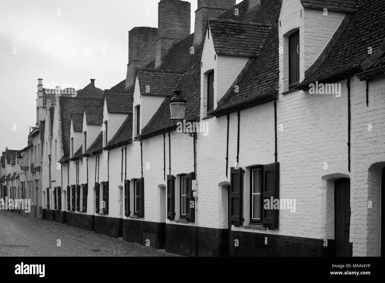 Balstraat, Brugge, Belgium: whitewashed cottages of the old Shoemakers' Guild almshouse, now housing the Museum voor Volkskunde - Stock Image