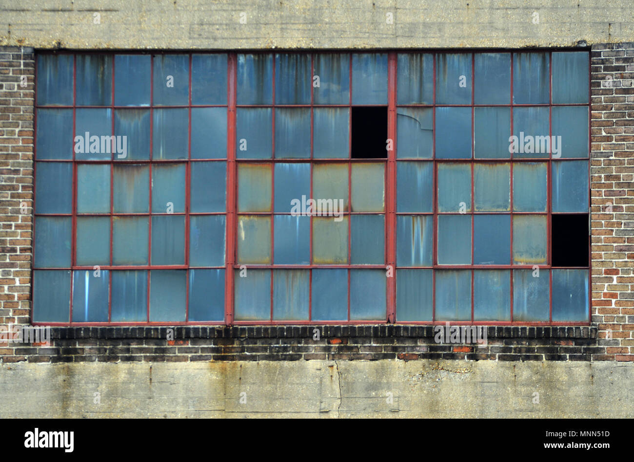 A large window on an old industrial building in the warehouse district of New Orleans Stock Photo