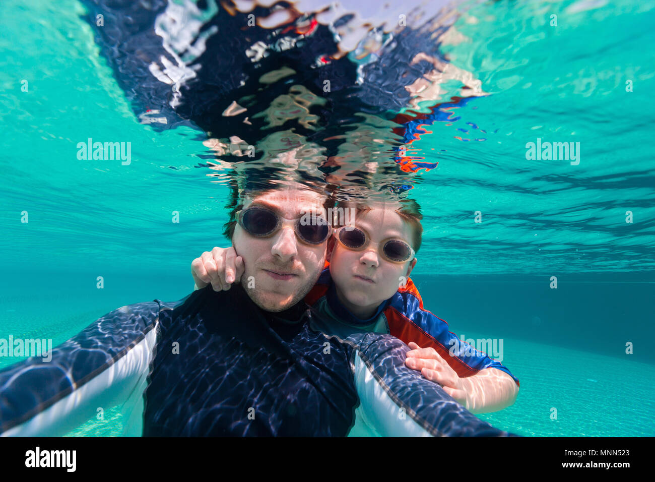 Father and son swimming underwater and making selfie - Stock Image