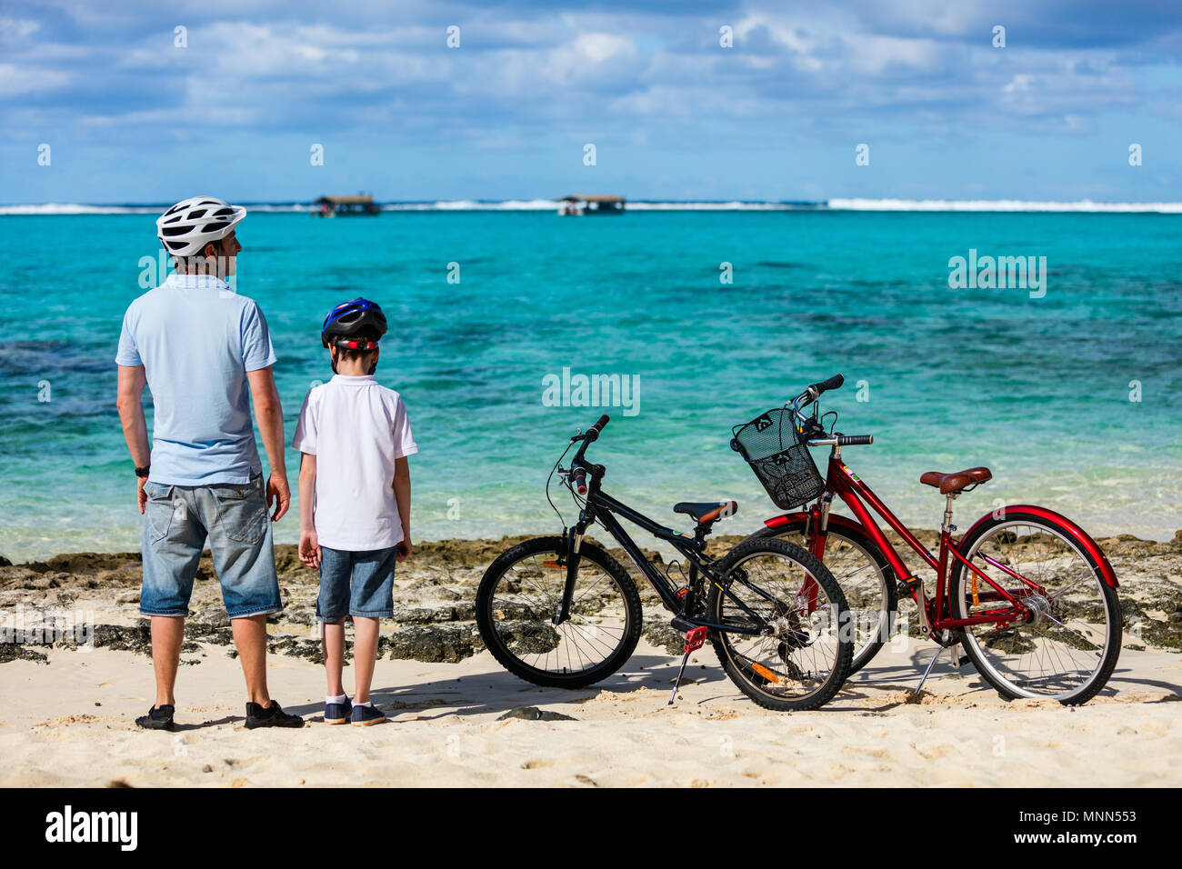 Father and kids enjoying sea view at tropical beach with their bikes parked nearby - Stock Image