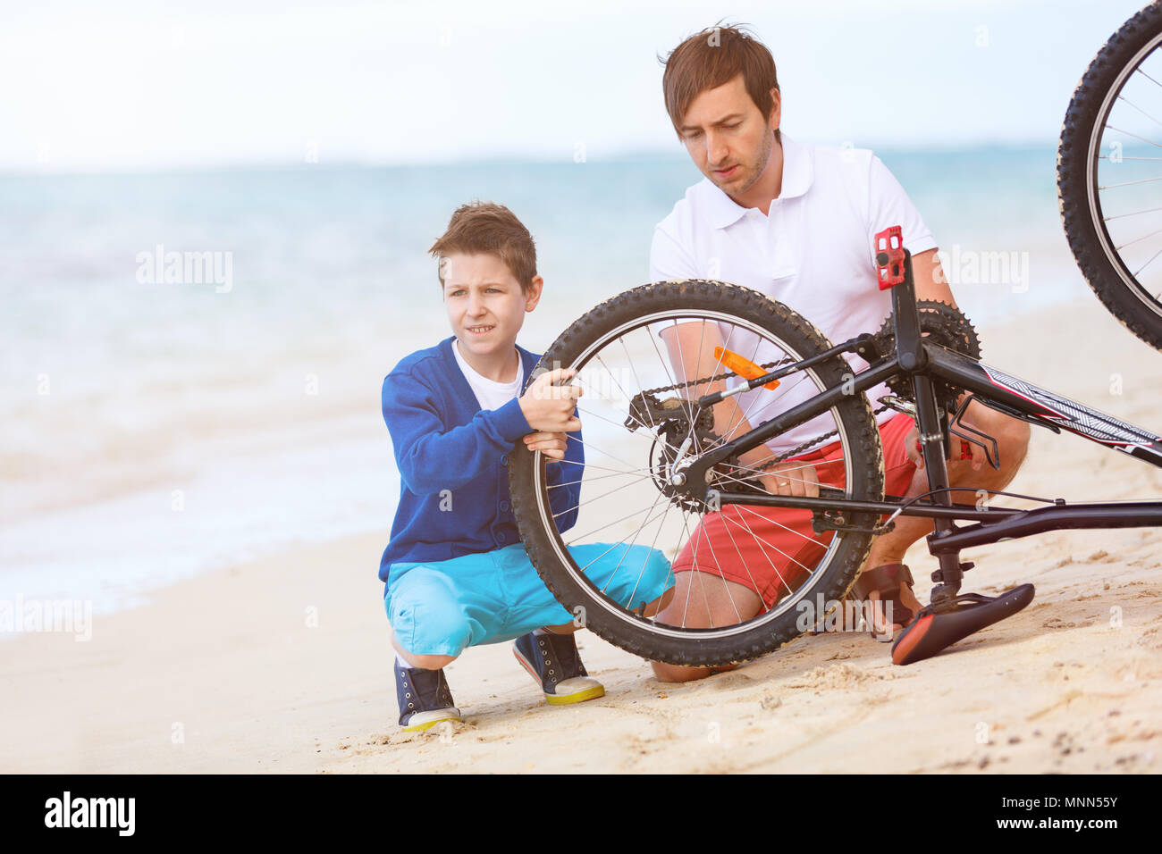 Teenage boy and his father repairing bicycle outdoors at summer Stock Photo