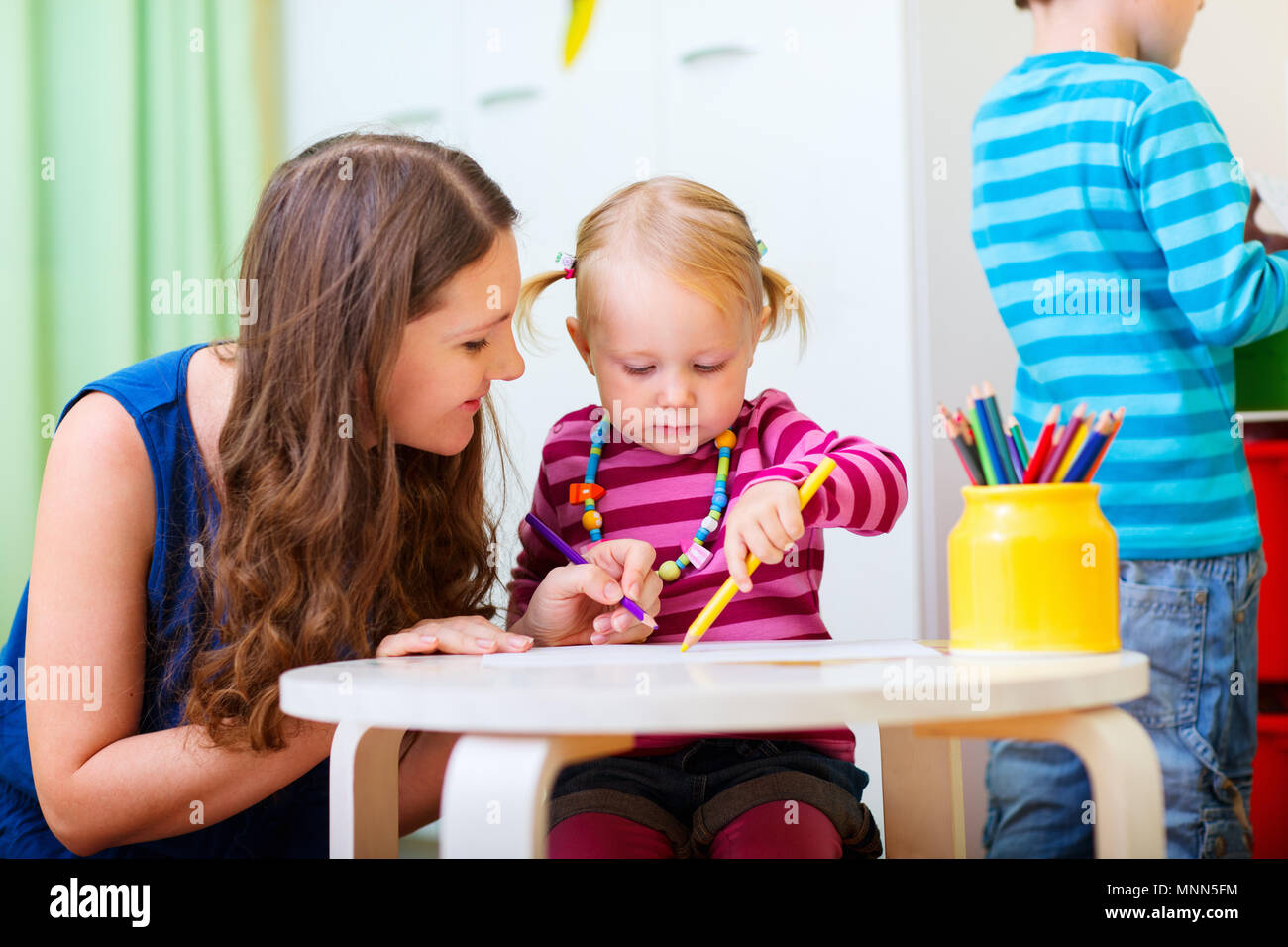 Young mother and her daughter drawing together. Also perfect for kindergarten daycare context. - Stock Image