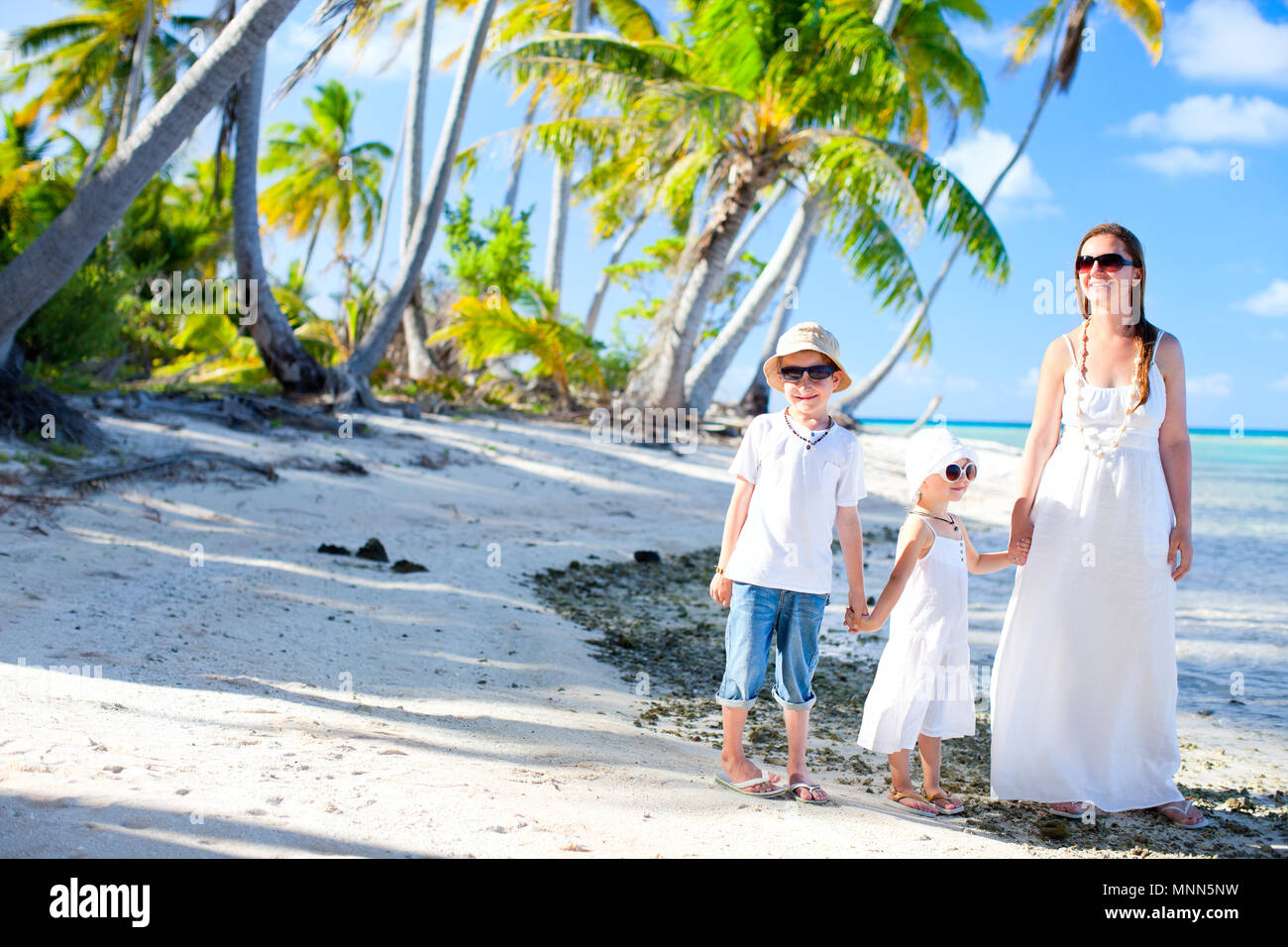 Beautiful family of mother and two kids on a deserted island - Stock Image