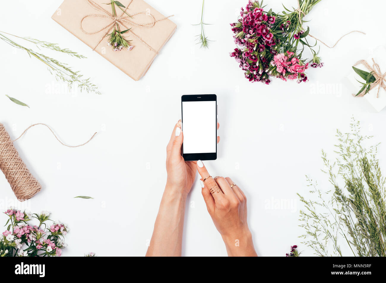 Woman uses smart phone among rustic gifts, flowers and field grass, top view. Flat lay festive composition female is going to touch screen with her in - Stock Image
