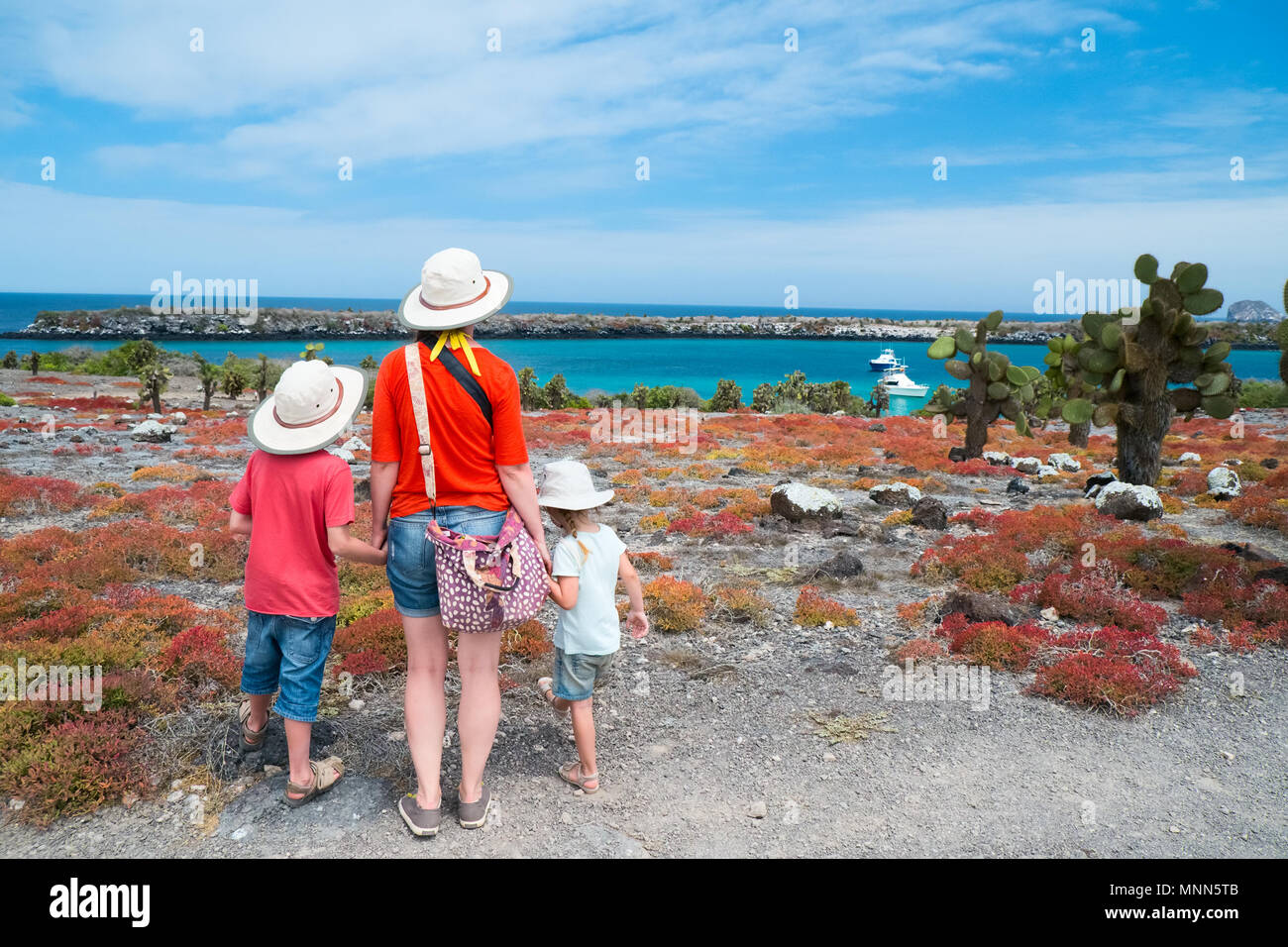 Mother and two kids hiking at scenic terrain - Stock Image