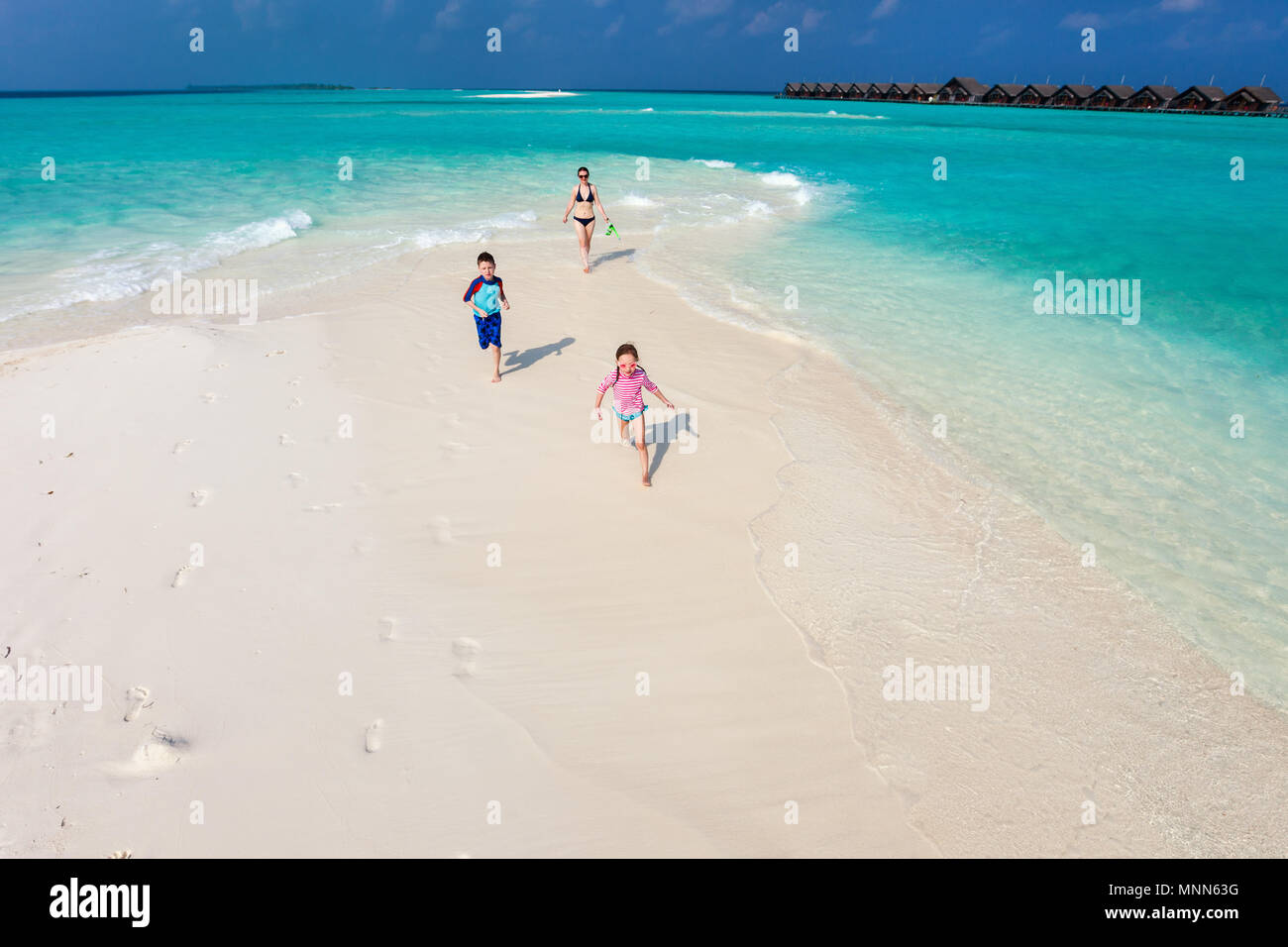 Above view of kids in a colorful sun protection swimwear running and having fun at beach - Stock Image