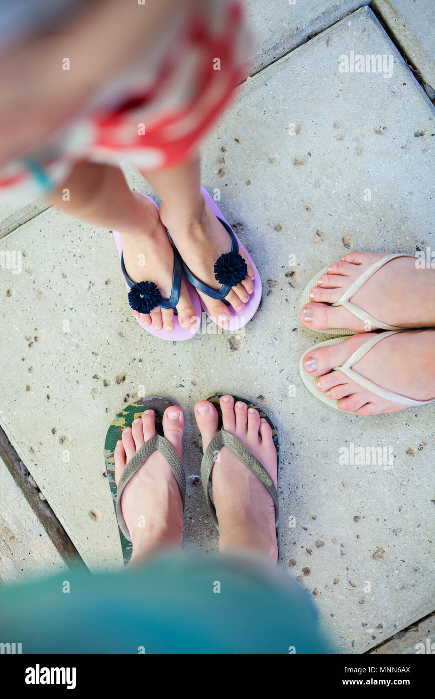 f0e4214b2641f2 Top view of family mother and kids feet in flip flops on summer vacation -  Stock