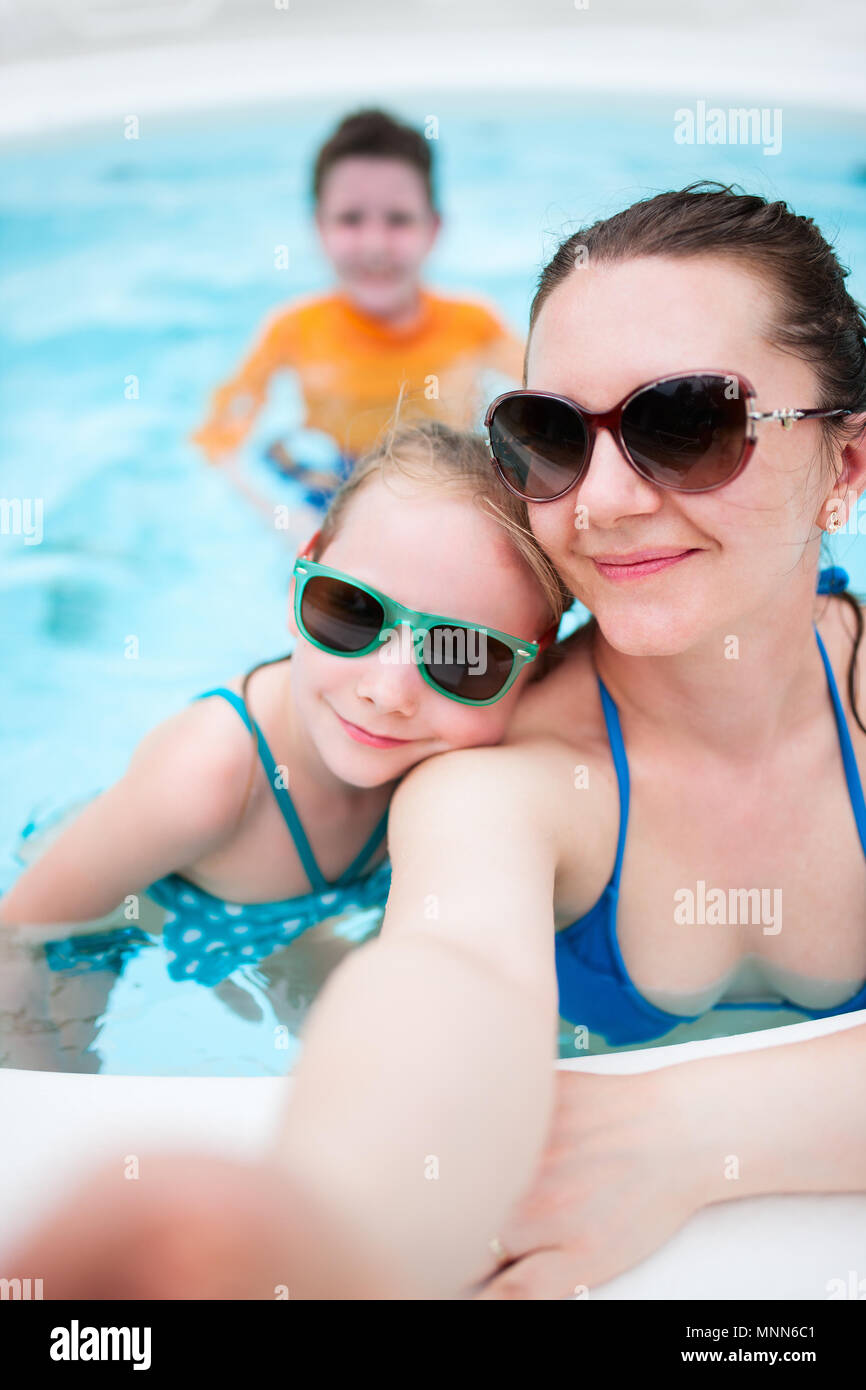 Happy mother and her kids at outdoors swimming pool taking selfie on tropical vacation - Stock Image