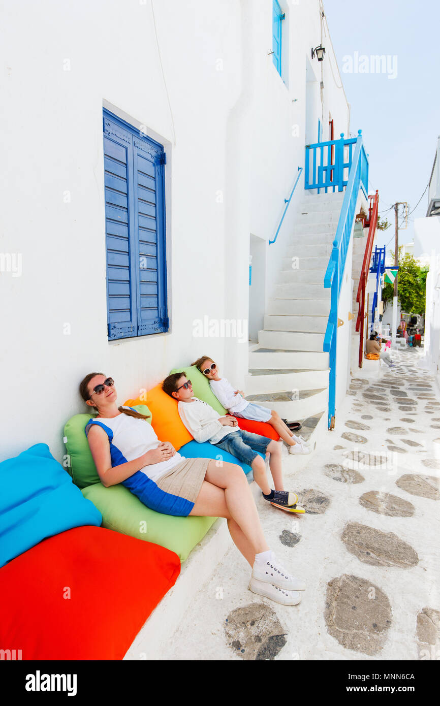 Family of mother and two kids relaxing on a colorful pillows at outdoor cafe on street of traditional greek village - Stock Image