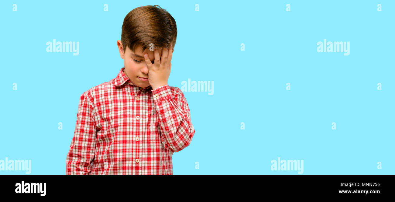 Handsome toddler child with green eyes stressful keeping hand on head, tired and frustrated over blue background - Stock Image