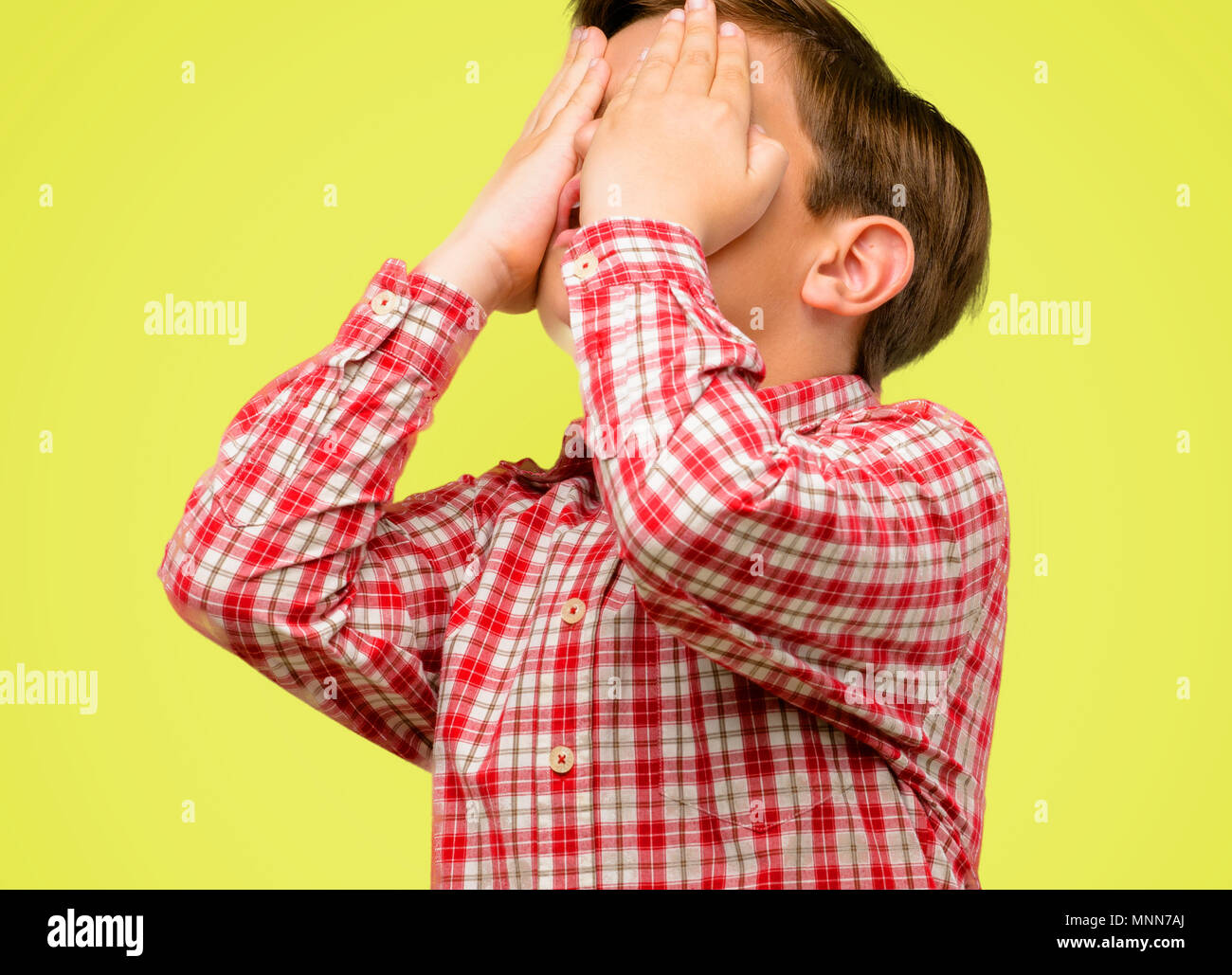 Handsome toddler child with green eyes stressful keeping hands on head, tired and frustrated over yellow background - Stock Image