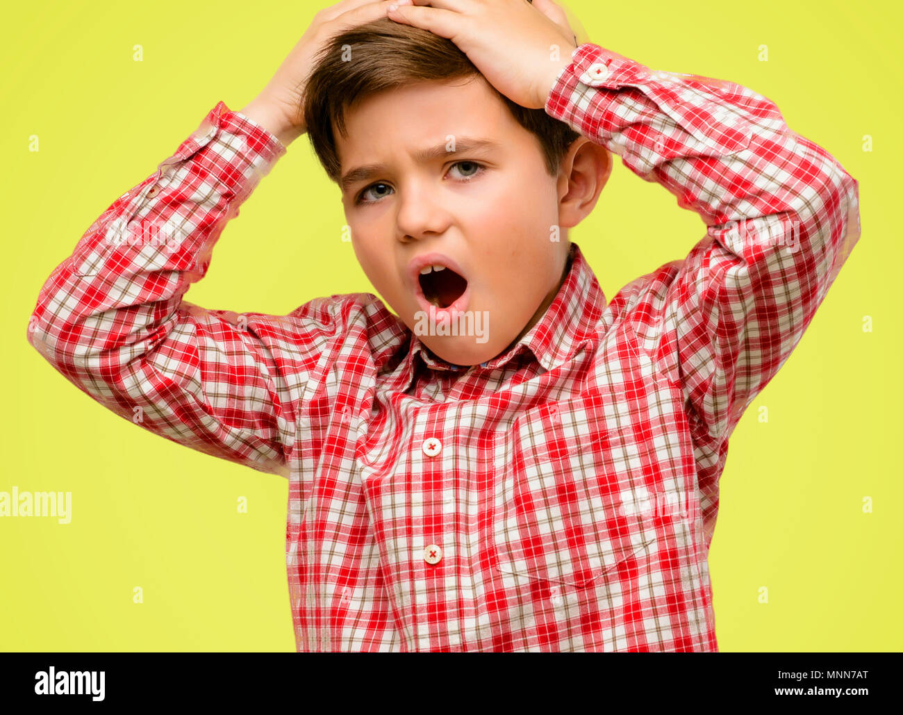 Handsome toddler child with green eyes stressful keeping hands on head, terrified in panic, shouting over yellow background - Stock Image