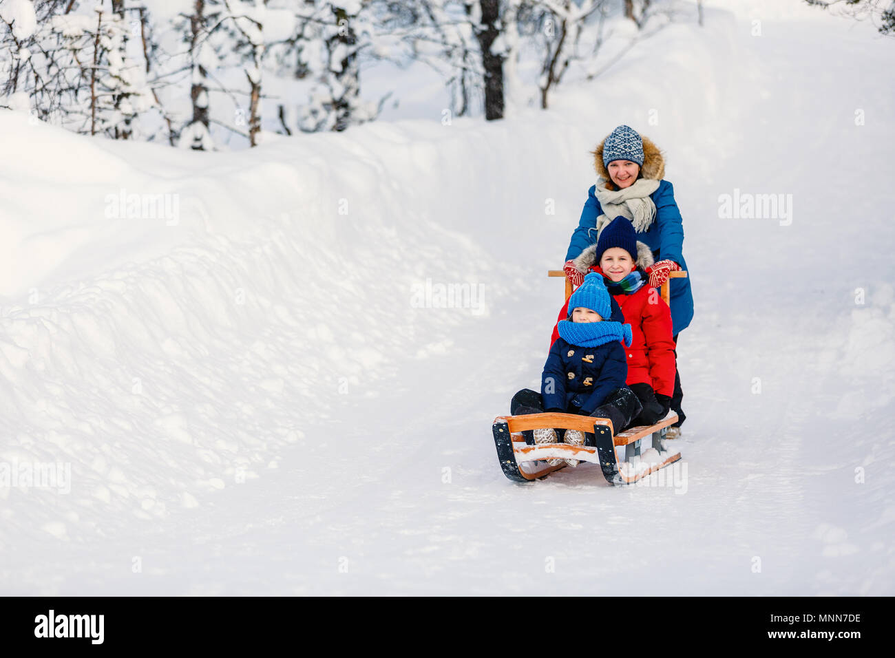 Beautiful family of mother and kids enjoying snowy winter day outdoors having fun sledging - Stock Image