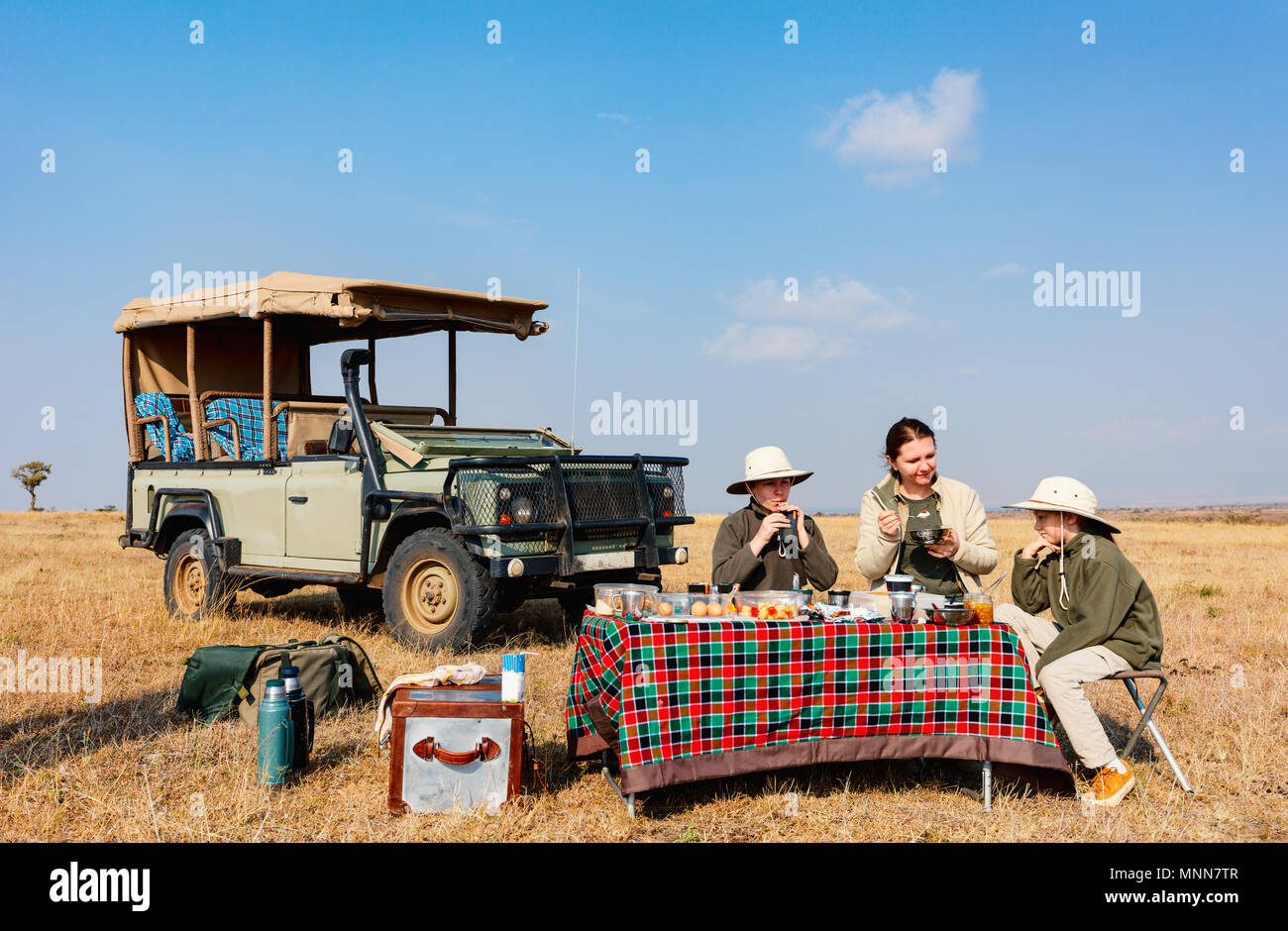 Family of mother and kids on African safari vacation enjoying bush breakfast - Stock Image