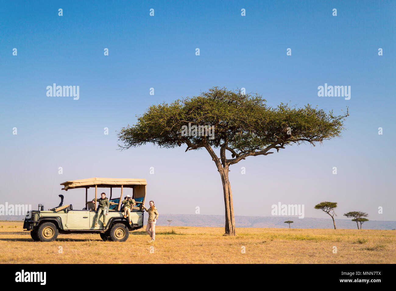 Family of mother and kids on African safari vacation enjoying morning game drive - Stock Image