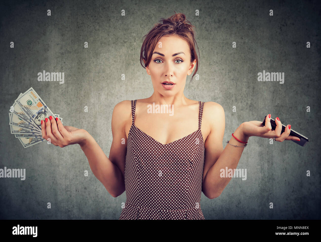 Confused displeased young woman holding smart phone and money dollar cash, unhappy with cellular service charges - Stock Image