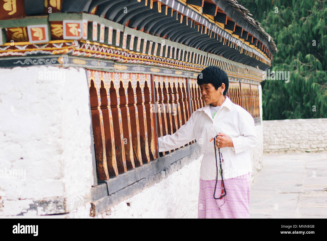 A Woman Spinning Prayer Wheels at Changangkha Lhakhang, Thimphu, Bhutan - Stock Image