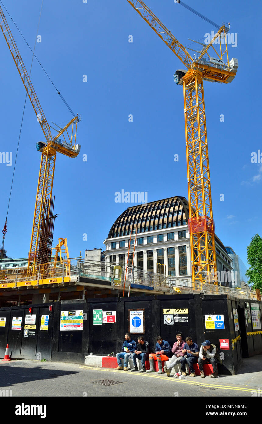 Construction work in Leicester Square, London, England, UK. Cranes abover the LSQLondon building (offices and retail) builders having a break - Stock Image