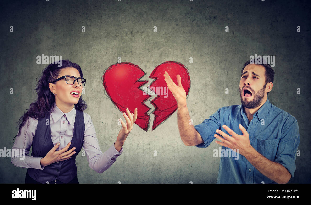 Desperate young heartbroken couple man and woman being separated - Stock Image