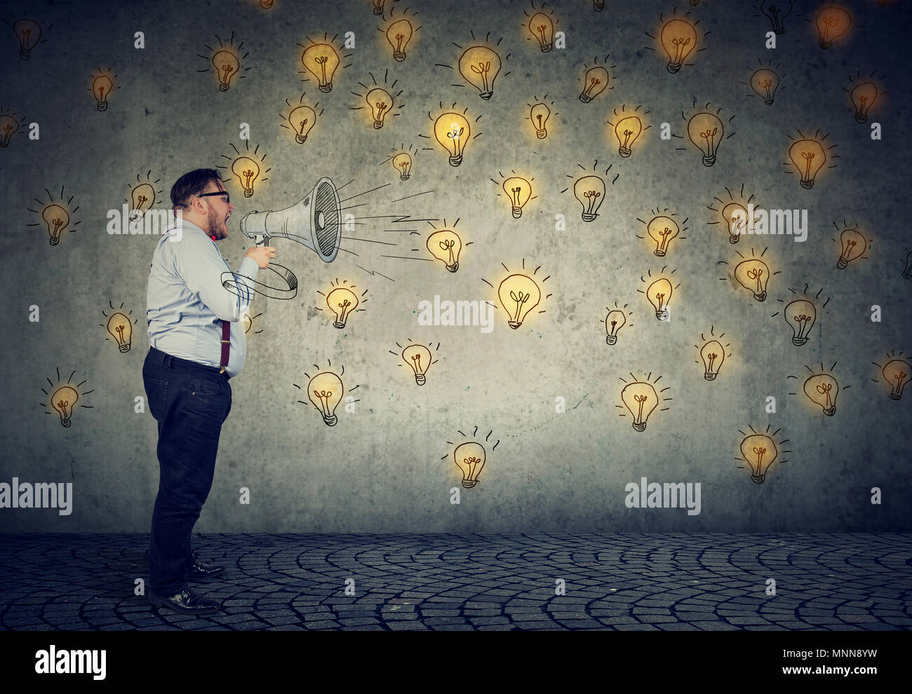 Man screaming out his ideas loud in megaphone spreading his ideas isolated on gray wall background - Stock Image